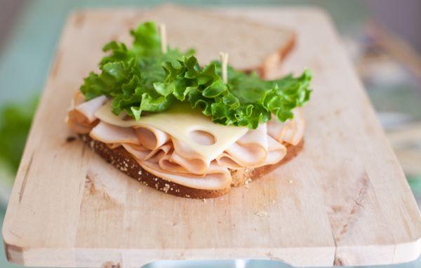 Сыр укладываем на колбасу, потом лист салата